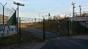 Das verschlossene Zugangstor, dahinter die S-Bahn-Strecke Richtung Bernau (S2).